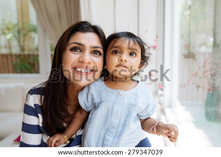 Portrait of curious little girl and her smiling mother looking up - stock photo