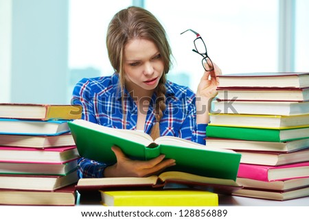 Portrait of curious student reading book in library - stock photo