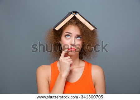 Portrait of curly annoyed bored tired young woman in orange top looking funny with book on head touching lips with forefinger and looking up - stock photo