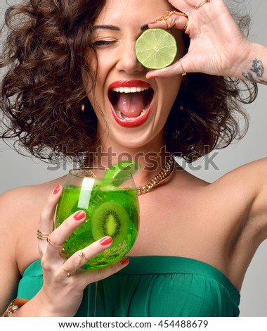 Portrait of curly hair woman in fashion cloth with mint mojito margarita cocktail with lime in hand screaming smiling laughing on gray background