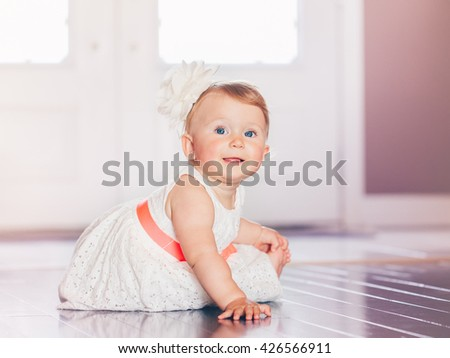 Portrait of cute adorable blonde Caucasian smiling baby child girl with blue eyes in white dress with red bow sitting on floor indoor looking in camera dreaming, fairy tale sun light from above behind - stock photo