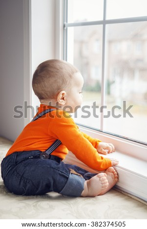 Portrait of cute adorable Caucasian baby boy with black eyes in orange shirt onesie, jeans with suspenders barefoot sitting on windowsill looking away, natural window light, lifestyle - stock photo