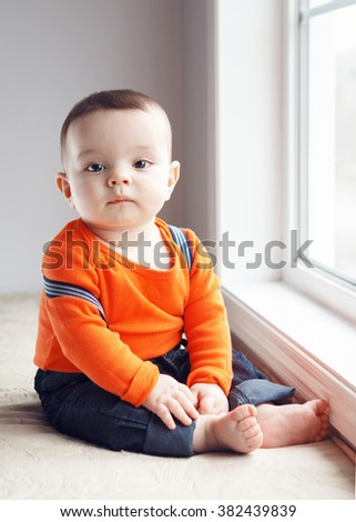Portrait of cute adorable Caucasian baby boy with black eyes in orange shirt onesie, jeans with suspenders barefoot sitting on windowsill looking in camera, natural window light, lifestyle - stock photo