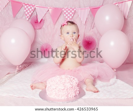 Portrait of cute adorable Caucasian baby girl with blue eyes in pink tutu skirt celebrating her first birthday with gourmet cake and balloons looking away, cake smash first year concept