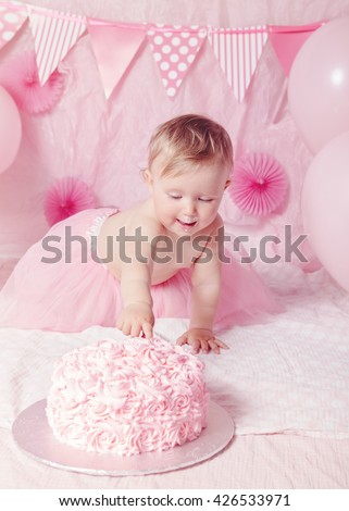 Portrait of cute adorable Caucasian baby girl with blue eyes in pink tutu skirt celebrating her first birthday with gourmet cake and balloons looking away, cake smash first year concept - stock photo