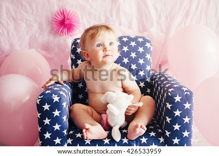 Portrait of cute adorable Caucasian baby girl with blue eyes sitting in blue children kids armchair with white stars celebrating her first birthday with balloons looking away - stock photo