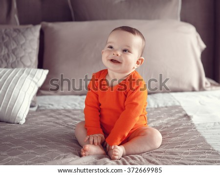 Portrait of cute adorable Caucasian smiling laughing baby boy girl with black brown eyes in orange red onesie shirt sitting on bed looking away from camera, natural window light, lifestyle - stock photo