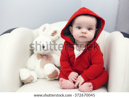 Portrait of cute adorable Caucasian smiling sad baby boy girl with black brown eyes in red hoodie shirt sitting in chair with toy looking directly in camera - stock photo