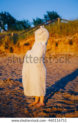 Portrait of cute adorable happy toddler little girl boy with beach towel hiding covering having fun, lifestyle sunset summer mood, toned with Instagram filters - stock photo