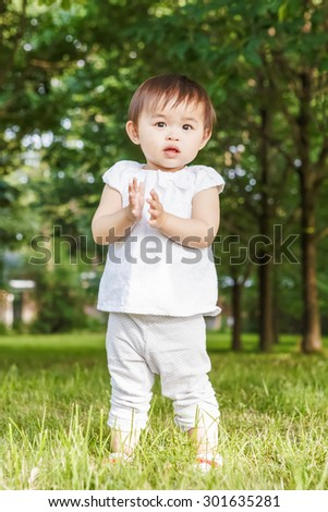 Portrait of cute adorable little Asian girl child baby one year old in white pants shirt, standing on field meadow grass on sunset playing clapping her hands - stock photo