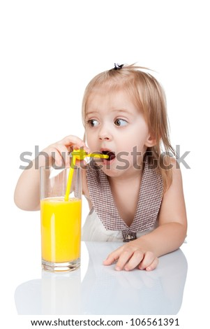 Portrait of cute adorable little girl drinking orange juice sitting at table isolated over white background