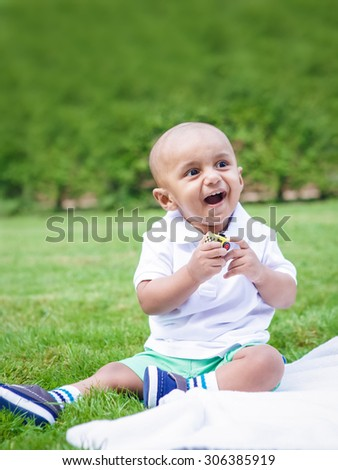 Portrait of cute adorable little indian South Asian infant boy in white shirt sitting on ground with toys in park green grass blanket outside on bright summer day smiling and playing - stock photo