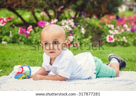 Portrait of cute adorable little indian South Asian or Middle Eastern infant boy in white shirt laying on ground with toys in park outside on bright summer day smiling and playing - stock photo