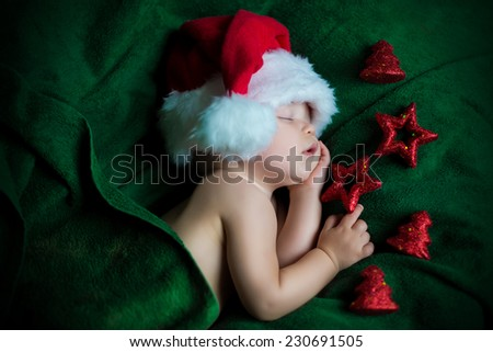 portrait of cute adorable sleeping baby in christmas hat laying on green - stock photo