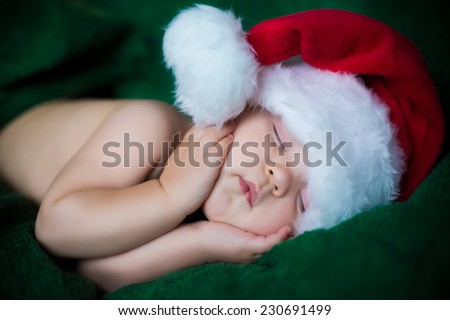 portrait of cute adorable sleeping baby in christmas hat laying on green touching face with her hands - stock photo