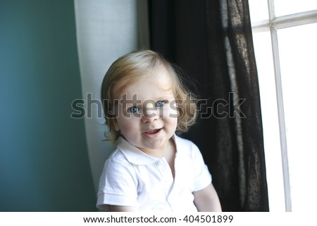 Portrait of cute adorable stylish Caucasian baby boy with blue eyes in hat, white shirt onesie, jeans with suspenders barefoot sitting on windowsill looking in camera, natural window light