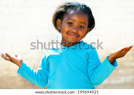 Portrait of cute African kid with arms open and wondering face expression.