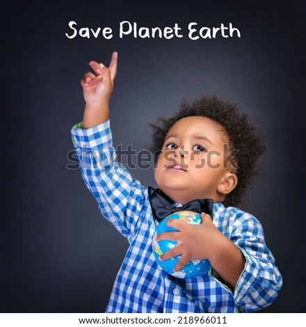 Portrait of cute African schoolboy raised up hand and globe in another hand isolated on blackboard background, text space, save Planet Earth concept - stock photo