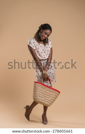 Portrait of cute african woman posing - standing with straw bag