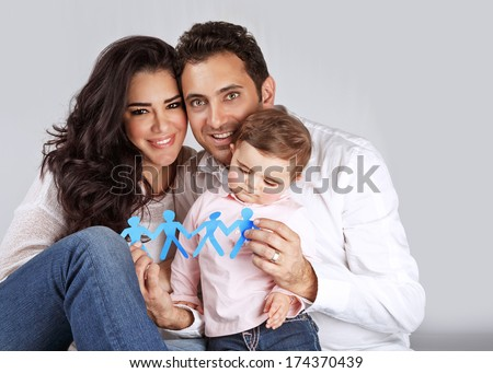 Portrait of cute arabic family sitting in the studio and holding in hands blue men-shape bonding paper, people unity concept - stock photo