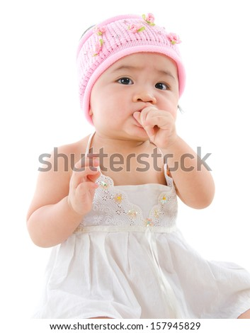 Portrait of cute Asian baby girl, eating on her own,  isolated on white background - stock photo