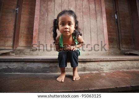 Portrait of cute Asian female child in green t-shirt sitting on street and looking at camera - stock photo