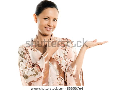 Portrait of cute Asian woman showing invisible product in studio isolated on white background - stock photo