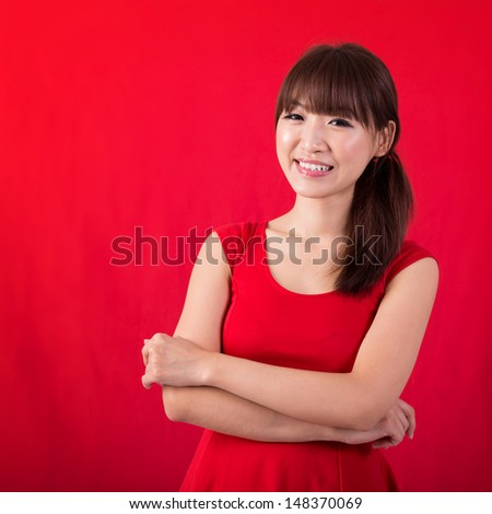 Portrait of cute Asian woman smiling wearing red dress isolated on red background. Asian female model. - stock photo