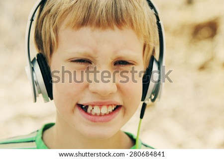 Portrait of cute autistic boy with headphones  - stock photo