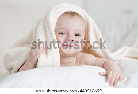 Portrait of cute baby boy lying under white blanket on bed