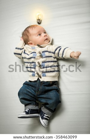 Portrait of cute baby boy posing on bed with glowing light bulb overhead - stock photo