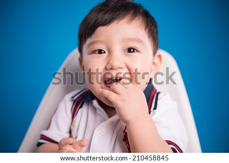 portrait of cute baby boy sucking his finger on blue background - stock photo