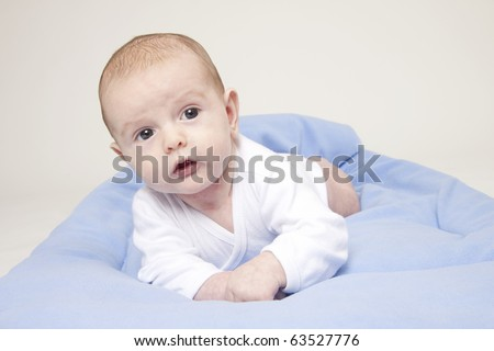 Portrait of cute baby boy with blue blanket and shoes - stock photo
