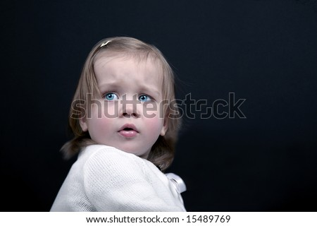 Portrait of cute baby girl looking a little scared - stock photo
