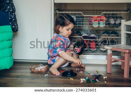 Portrait of cute baby girl playing with hair clips collection sitting in a wooden floor at home - stock photo
