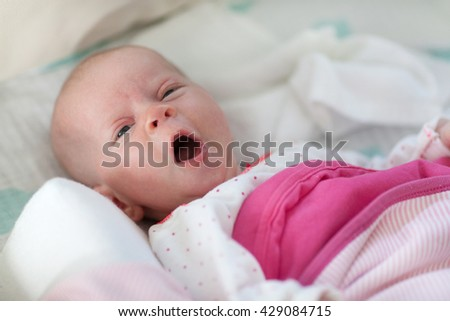 Portrait of cute baby girl yawning.