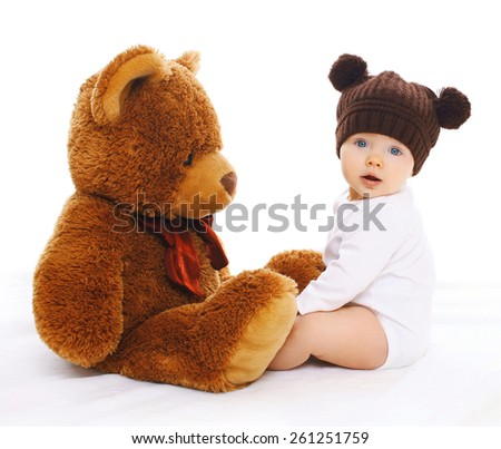 Portrait of cute baby in knitted brown hat with big teddy bear - stock photo