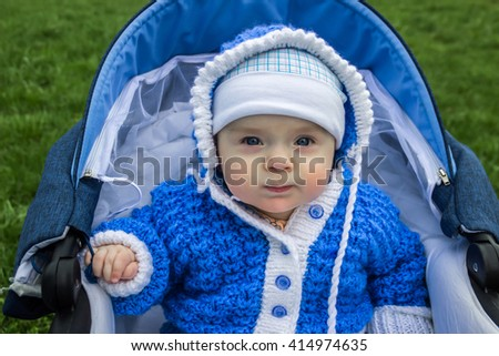 Portrait of cute baby sitting in stroller. Age of the baby is 6 months. - stock photo