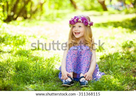 Portrait of cute blond girl dressed wreath of lilac on a head in green field - stock photo