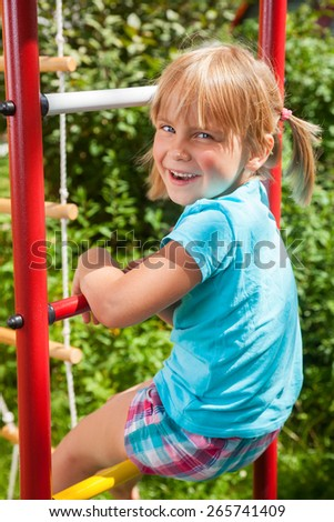 Portrait of cute blond girl with blue eyes wearing blue tshirt sitting on monkey bars on a summer day. Girl looking at camera smiling. Green leaves a seen in the background. - stock photo