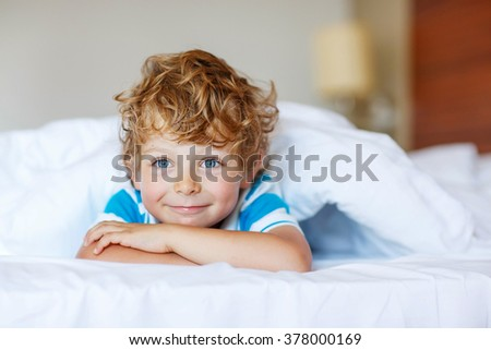 Portrait of cute blond kid boy in his white bed. Little happy looking at the camera and smiling. Family, vacation, happy childhood concept - stock photo