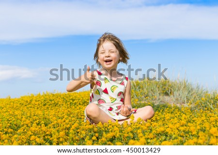 portrait of cute blond little girl in preschool age looking satisfied and playing in rural field with many small bright yellow flowers with blue sky background - stock photo