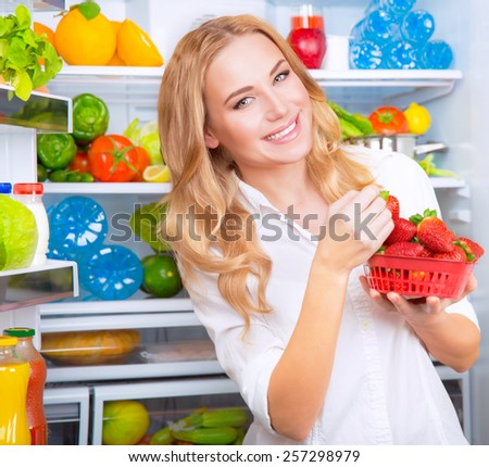 Portrait of cute blond woman standing near open refrigerator full of fruits and vegetables and eating fresh red ripe strawberries - stock photo