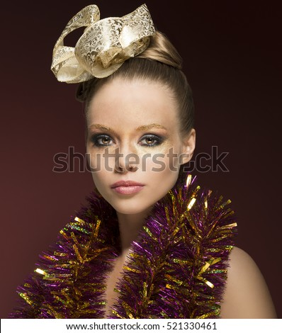portrait of cute blonde female posing on red background with creative glossy golden make-up, ribbon in the hairdo and sparkly tinsel on nude shoulders.
