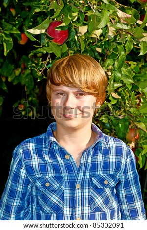 portrait of cute boy in leaves of the tree - stock photo