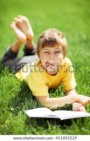 Portrait of cute boy lying on the grass with the book - stock photo