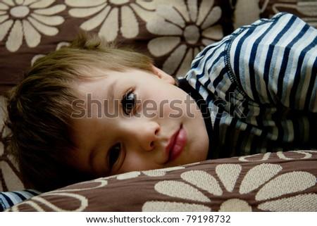 Portrait of cute boy on a sofa - stock photo
