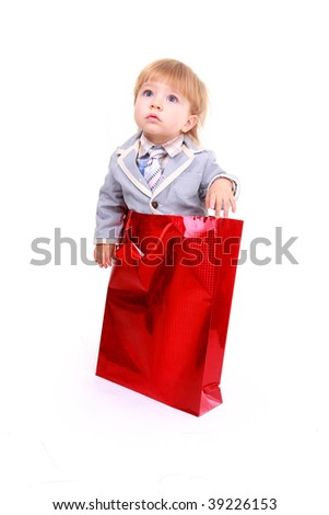 Portrait of cute boy on shopping bag isolated on white background - stock photo
