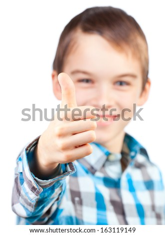 Portrait of cute boy showing thumb up on white background