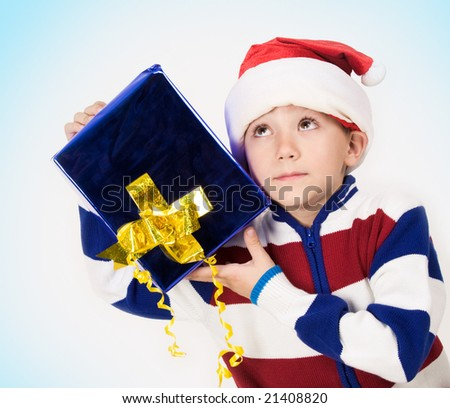 Portrait of cute boy with giftbox in hands and listening to something in it
